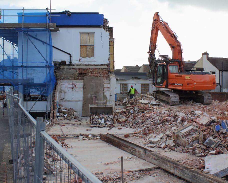 Orange tractor demolishing a building - Big Easy Demolition